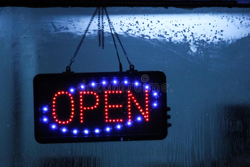 Neontecknet som är öppet på fönster, shoppar arkivfoto