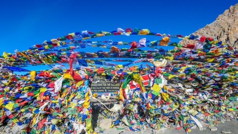 Nepal - bönflaggor upptill av det Thorung Lapasserandet arkivfoton