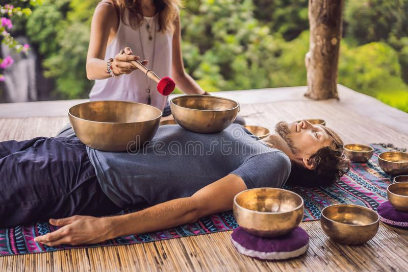 Nepal Buddha copper singing bowl at spa salon. Young beautiful man doing massage therapy singing bowls in the Spa. Nepal Buddha copper singing bowl at spa salon stock photos