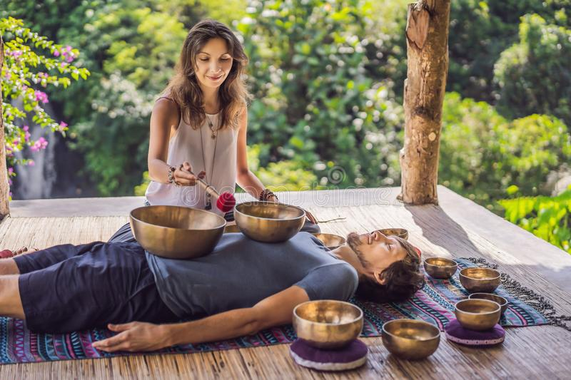 Nepal Buddha copper singing bowl at spa salon. Young beautiful man doing massage therapy singing bowls in the Spa. Nepal Buddha copper singing bowl at spa salon royalty free stock photography