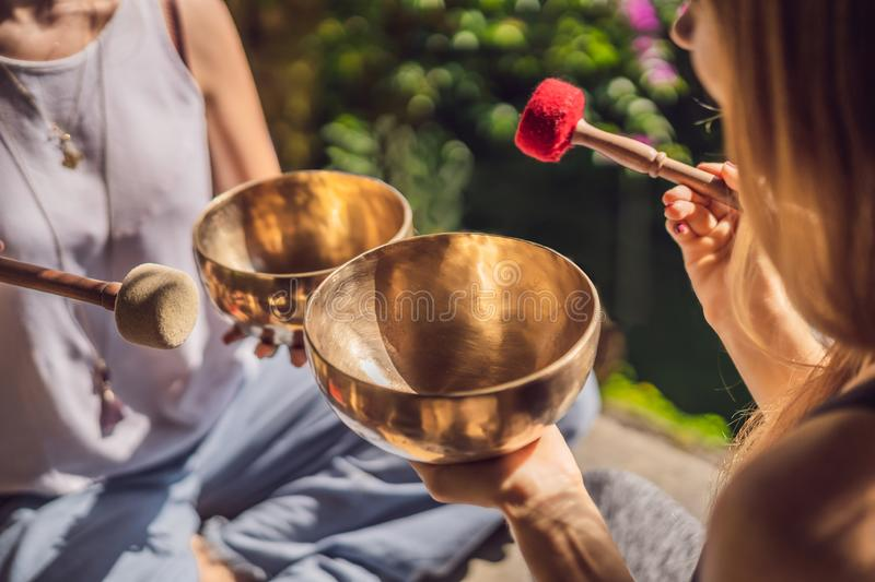 Nepal Buddha copper singing bowl at spa salon. Young beautiful woman doing massage therapy singing bowls in the Spa. Nepal Buddha copper singing bowl at spa royalty free stock photos
