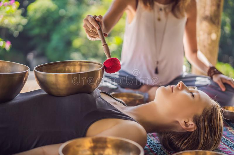 Nepal Buddha copper singing bowl at spa salon. Young beautiful woman doing massage therapy singing bowls in the Spa. Nepal Buddha copper singing bowl at spa stock image