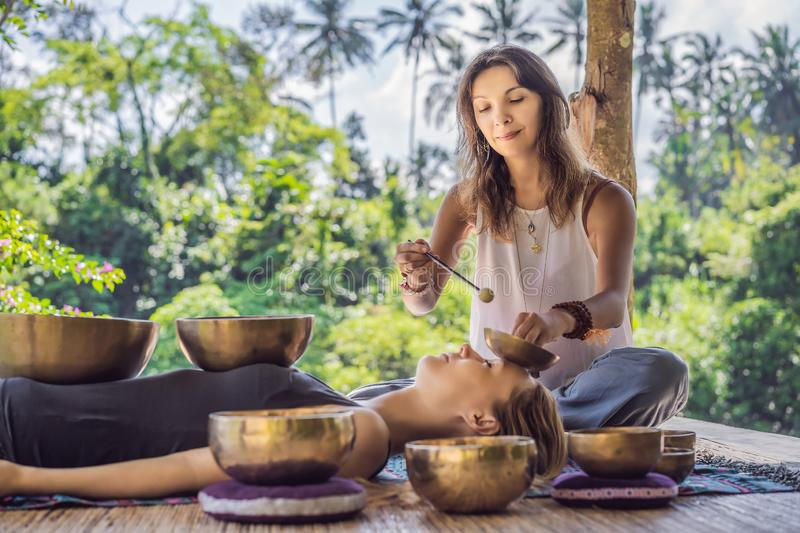 Nepal Buddha copper singing bowl at spa salon. Young beautiful woman doing massage therapy singing bowls in the Spa. Nepal Buddha copper singing bowl at spa royalty free stock photo