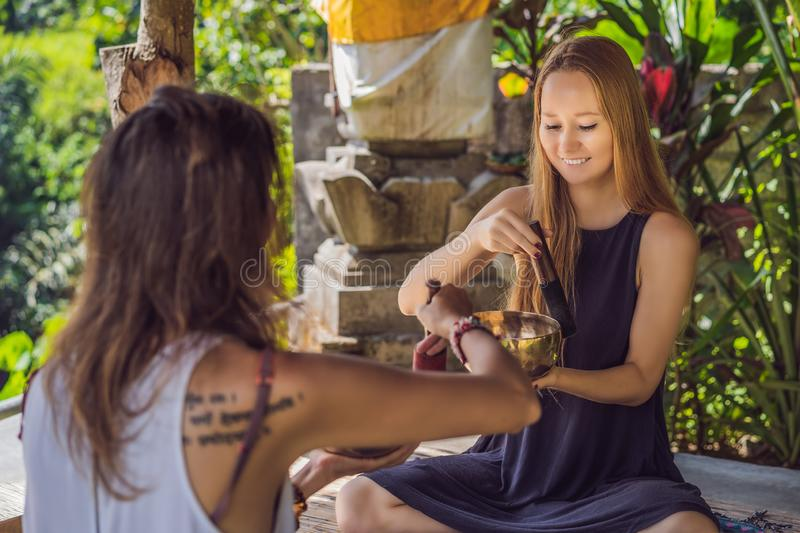 Nepal Buddha copper singing bowl at spa salon. Young beautiful woman doing massage therapy singing bowls in the Spa. Nepal Buddha copper singing bowl at spa stock photography