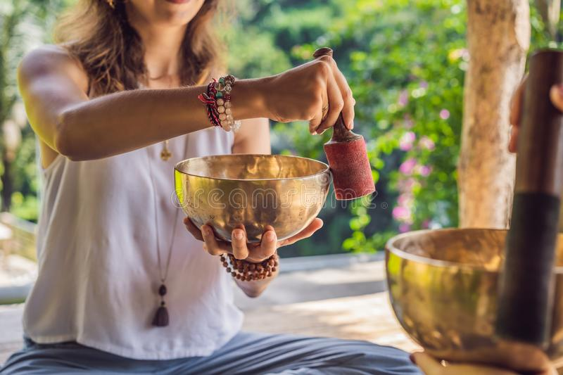 Nepal Buddha copper singing bowl at spa salon. Young beautiful woman doing massage therapy singing bowls in the Spa. Nepal Buddha copper singing bowl at spa royalty free stock image