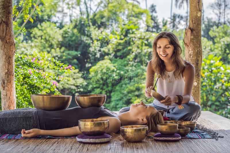 Nepal Buddha copper singing bowl at spa salon. Young beautiful woman doing massage therapy singing bowls in the Spa. Nepal Buddha copper singing bowl at spa royalty free stock images