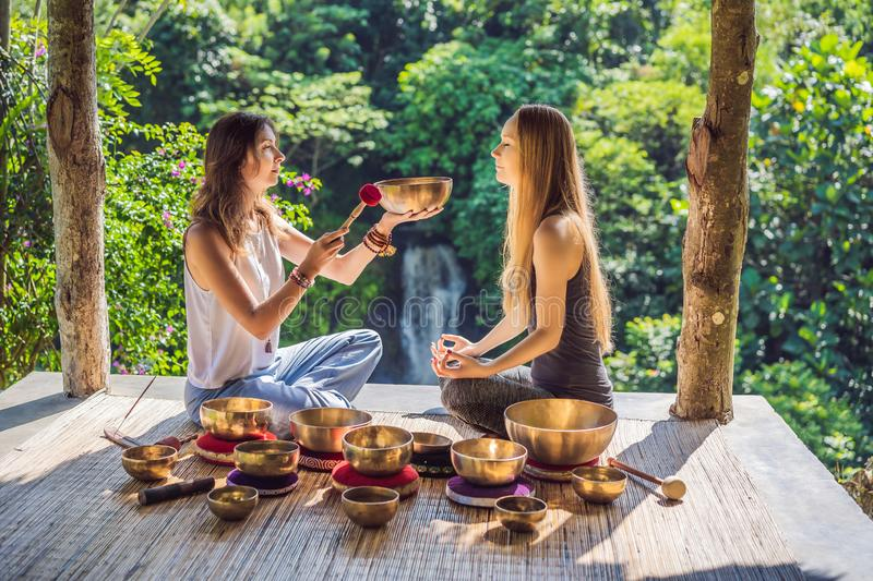 Nepal Buddha copper singing bowl at spa salon. Young beautiful woman doing massage therapy singing bowls in the Spa. Nepal Buddha copper singing bowl at spa stock images
