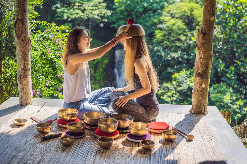 Nepal Buddha copper singing bowl at spa salon. Young beautiful woman doing massage therapy singing bowls in the Spa. Nepal Buddha copper singing bowl at spa stock photos