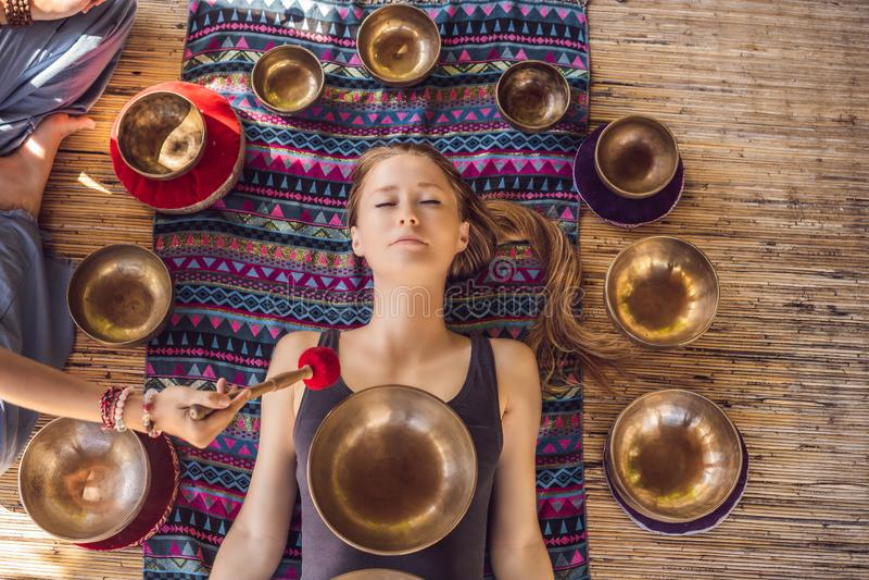 Nepal Buddhakopparsjunga bunke på brunnsortsalongen Ung härlig kvinna som gör massageterapi som sjunger bunkar i Spa arkivbild