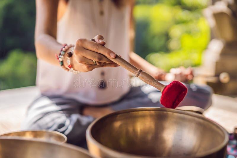 Nepal Buddhakopparsjunga bunke på brunnsortsalongen Ung härlig kvinna som gör massageterapi som sjunger bunkar i Spa royaltyfri fotografi