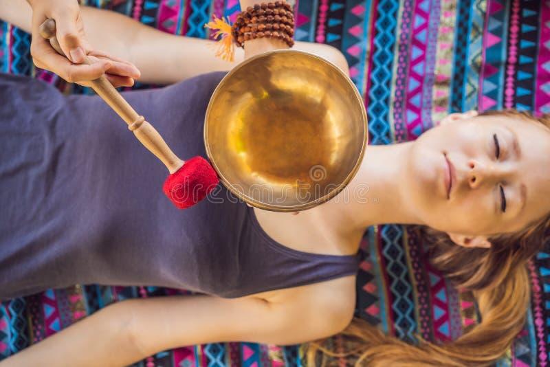 Nepal Buddhakopparsjunga bunke på brunnsortsalongen Ung härlig kvinna som gör massageterapi som sjunger bunkar i Spa royaltyfri foto