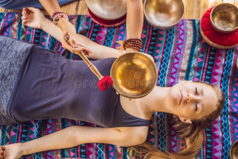 Nepal Buddhakopparsjunga bunke på brunnsortsalongen Ung härlig kvinna som gör massageterapi som sjunger bunkar i Spa arkivfoto