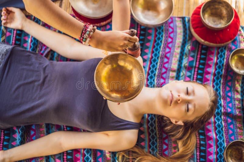 Nepal Buddhakopparsjunga bunke på brunnsortsalongen Ung härlig kvinna som gör massageterapi som sjunger bunkar i Spa royaltyfri bild