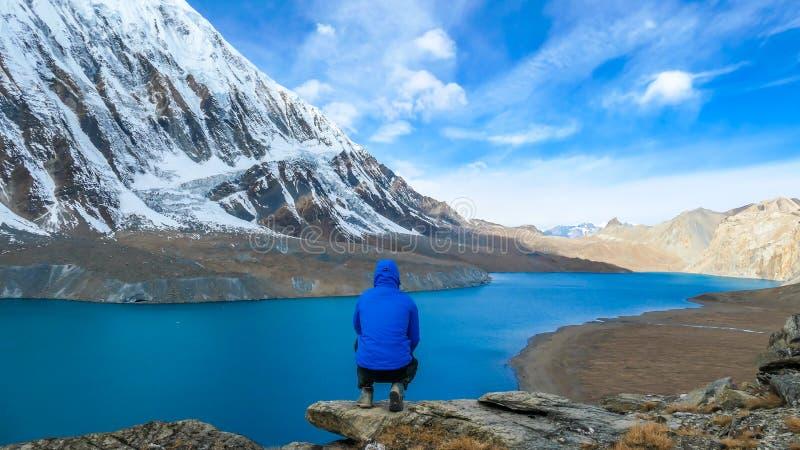 Nepal - den unga mannen som squatting på, vaggar framme av Tilicho sjön royaltyfria foton
