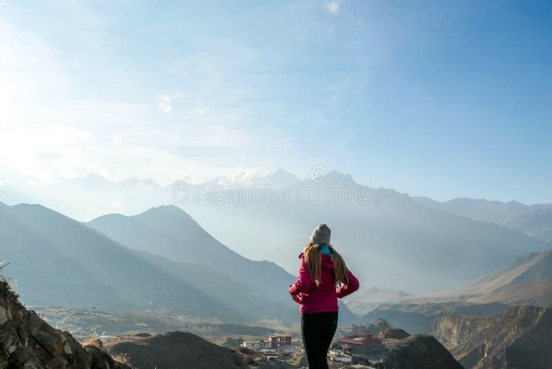 Nepal - een meisje die en de mening over lang Himalayagebergte bevinden zich bewonderen royalty-vrije stock fotografie