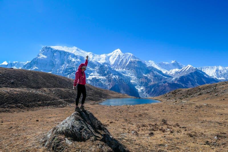 Nepal - eine Mädchenstellung am Felsen durch den Ice See lizenzfreies stockbild