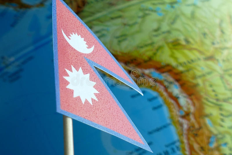 Nepal flag with a globe map as a background. Macro stock photography