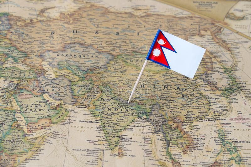 Nepal flag pin on a world map. Nepal paper flag pin on an ancient world map. Officially the Federal Democratic Republic of Nepal, it is a landlocked central stock image