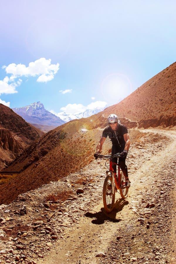 Nepal, Himalaja, das Königreich des oberen Mustangs - April 2015: Ein Mountainbikeradfahrer steigt die Gebirgsstraße ab lizenzfreies stockfoto