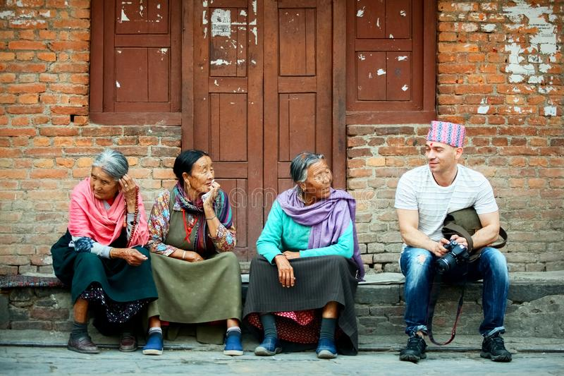 Nepal, Kathmandu, Palast-Quadrat - 26. April 2014: Europäischer Tourist spricht mit Einheimischen auf der Straße der alten Stadt stockfotografie
