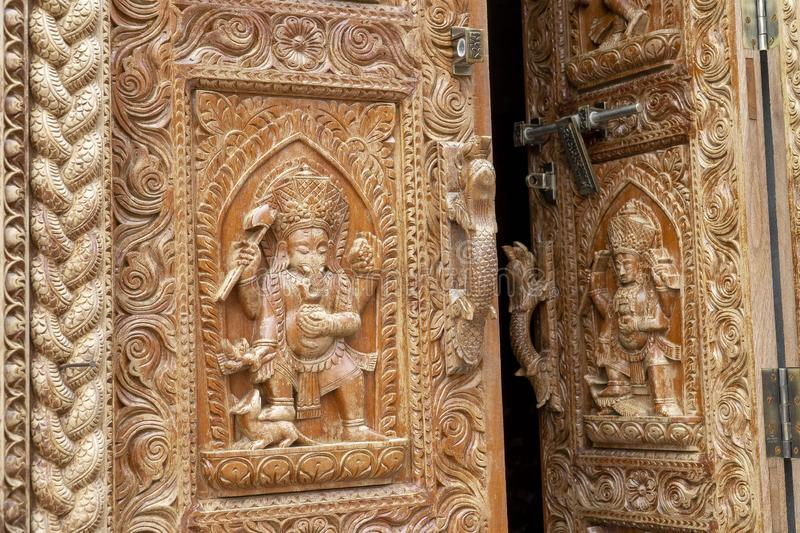 Nepal Kathmandu temple of Changu Narayan, view of an ancient wooden door carved with sacred images.  royalty free stock image