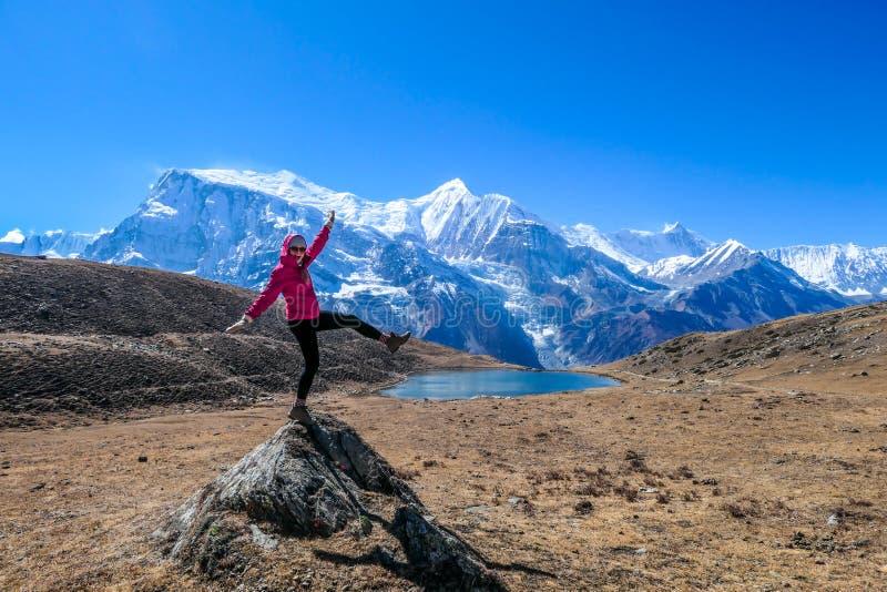 Nepal - Mädchen, das auf einem Felsen im nahe gelegenen des Ice Sees, Annpurna-Stromkreis-Wanderung im Himalaja balanciert lizenzfreies stockfoto