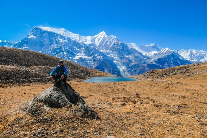 Nepal - Mann, der auf dem stne, Ice See, Annapurna-Stromkreis-Wanderung sitzt lizenzfreies stockbild