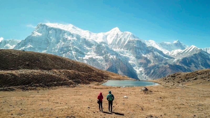 Nepal - Paar und der Ice See mit der Ansicht über Annapurna-Kette stockfotos