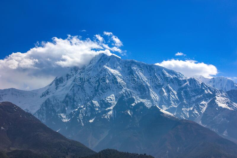 Nepal snowy mountains against the blue sky with clouds.  stock photography