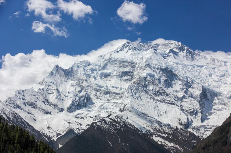Nepal snowy mountains against the blue sky with clouds.  royalty free stock image