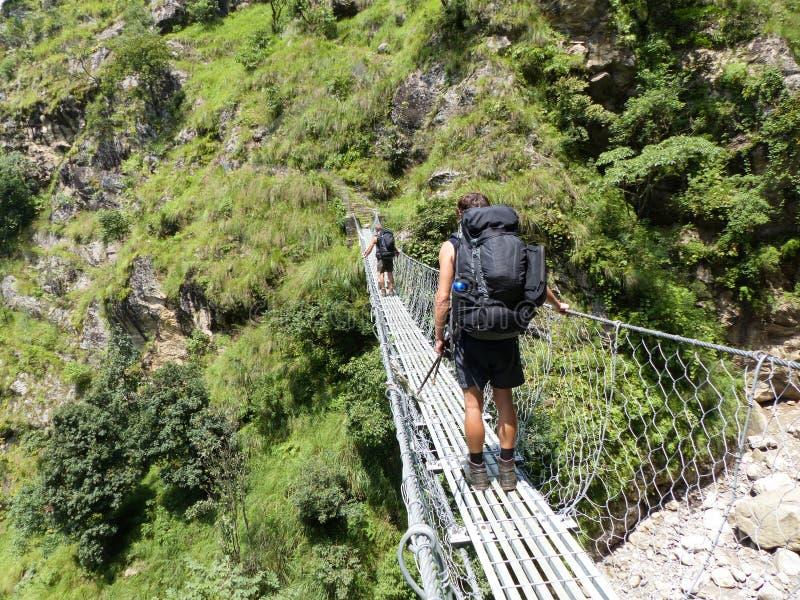 Nepal trekking. Tourist passing suspension bridge in Marsyangdi river valley - Annapurna Circuit trek stock image