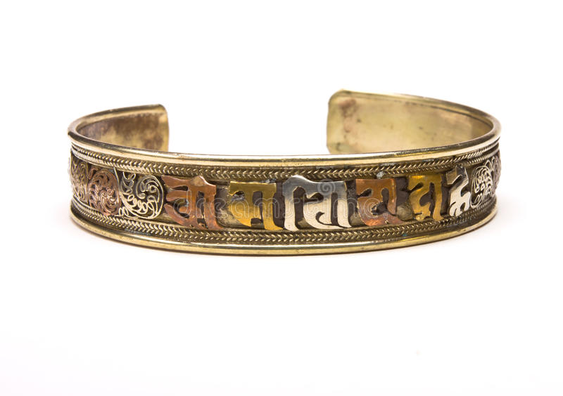 Nepalese bangle. 3 coloured metal Torque bangle from Nepal with mantra motif from low perspective isolated against white background stock photography
