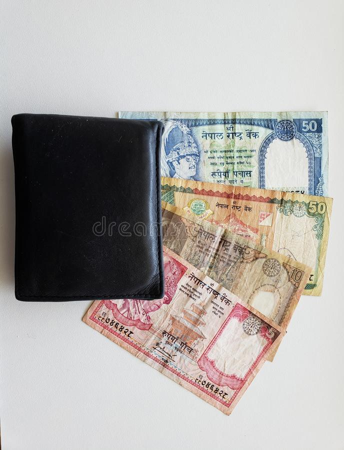 Nepalese banknotes of different denominations and black leather wallet stock images