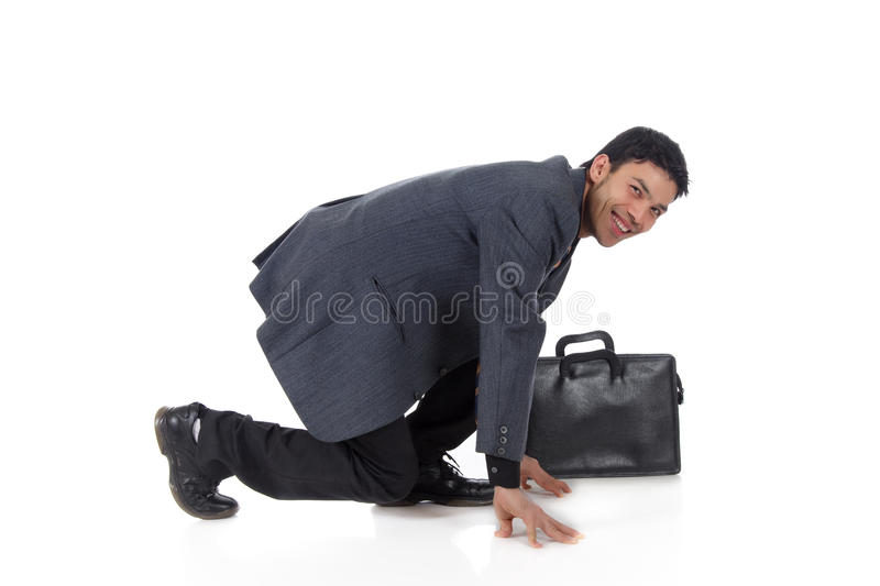 Nepalese businessman start position. Attractive young nepalese businessman with suitcase kneeling, ready for race. Start position. Studio shot. White background stock photography