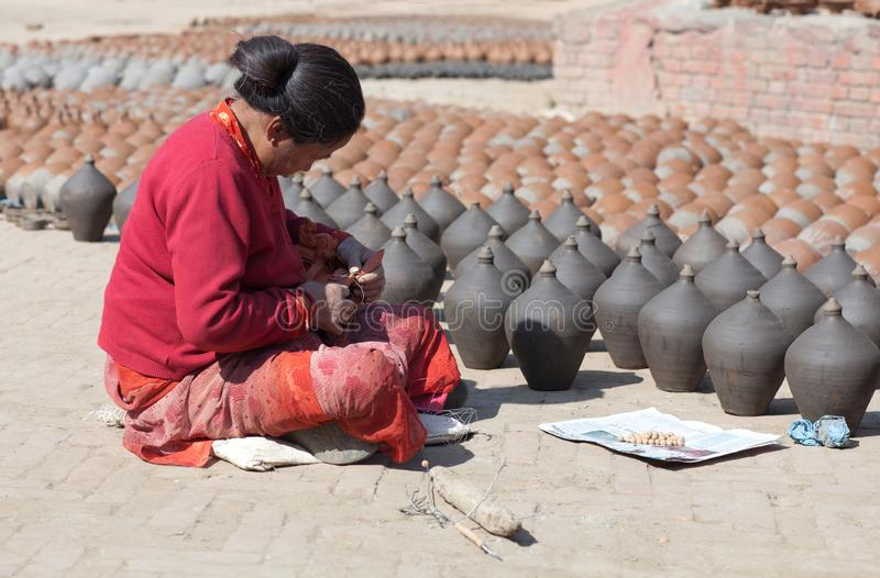 Nepalese craftswoman in Bhaktapur, Nepal. BHAKTAPUR, NEPAL - JANUARY 23, 2017: Nepalese craftswoman poses for a photo at work on famous Pottery Square royalty free stock photo