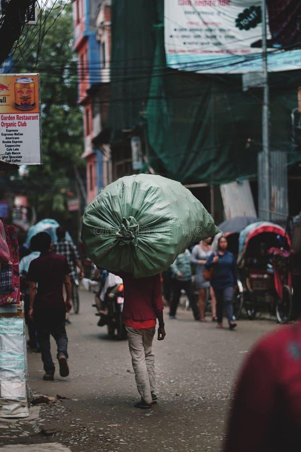 Nepalese, der die schweren und großen Lasten führen Thamel-Straße trägt stockfotografie