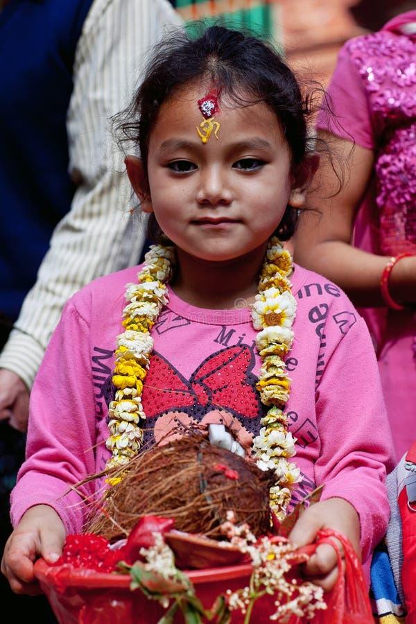 Nepalese girl. DAKSHINKALI, NEPAL - MAY 11: Nepalese girl carries offering to Dakshinkali Temple on May 11, 2013 in Dakshinkali village, Kathmandu valley, Nepal royalty free stock photos