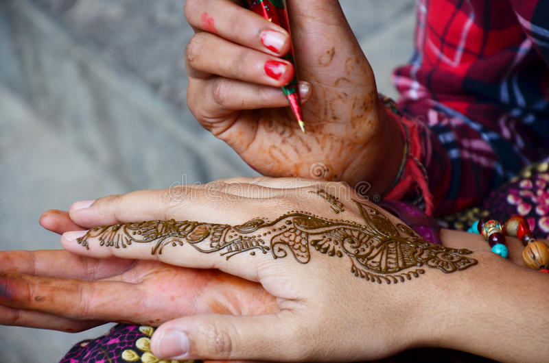 Nepalese girl paint Mehndi or Henna india style for thai traveler. Women at Thamel market street. Mehndi or henna is a paste that is bought in a cone-shaped royalty free stock image
