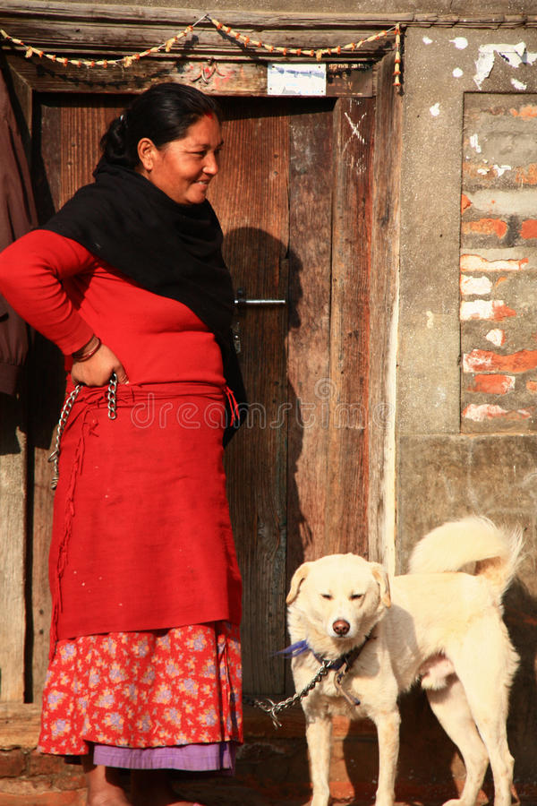 Nepalese lady and a dog. A Nepalese lady and a dog in a village near Kathmandu stock photos