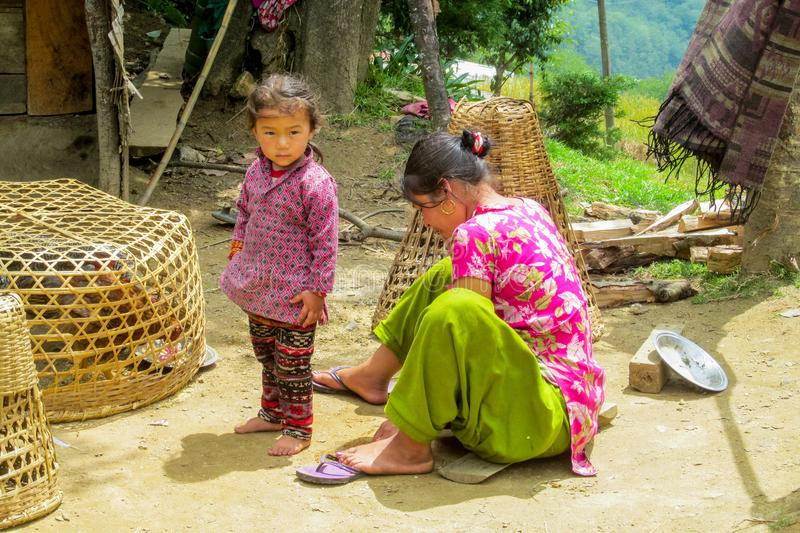 Nepalese little girl and her mother in the village. Children, small kid portrait outside in Nepal royalty free stock images