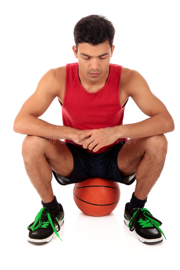 Nepalese man basketball player. Attractive Nepalese man basketball player sitting on his ball, meditating. Studio shot. White background royalty free stock photos