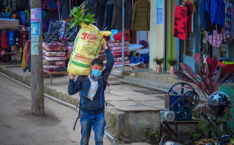 Nepalese man carrying a heavy bag of rice on his shoulder. Khandbari, Sankhuwasabha District, Nepal - 11/15/2017 : Man with mouth mask carrying a heavy bag of royalty free stock images
