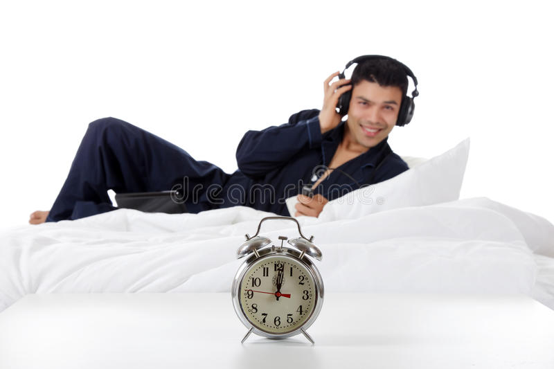 Nepalese man in pajamas, clock. Handsome young nepalese man wearing pajamas, in bed with laptop, listening in headphones. Retro clock on table. Focus on clock stock image