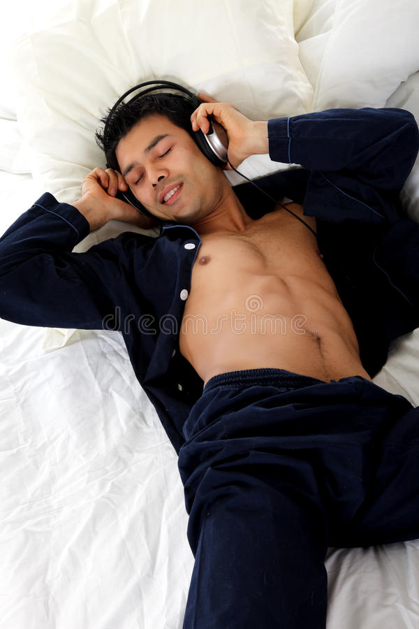 Nepalese man in pajamas, headphones royalty free stock image