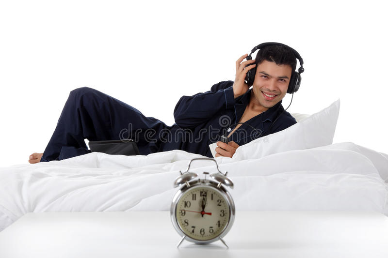 Nepalese man in pajamas, laptop. Handsome young nepalese man wearing pajamas, in bed with laptop, listening in headphones. Retro clock on table. Focus on man royalty free stock photography