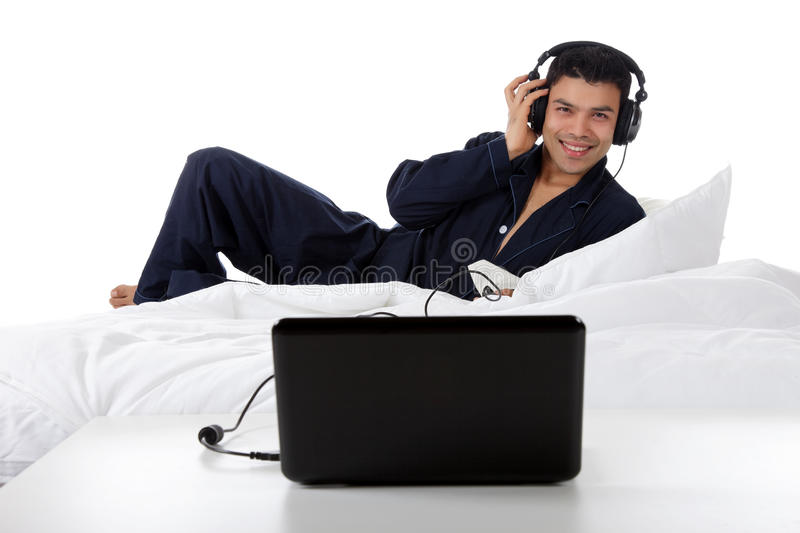 Nepalese man in pajamas, laptop. Handsome young nepalese man in pajamas with headphones and laptop, relaxing in bed and listening music from the internet. Focus stock images