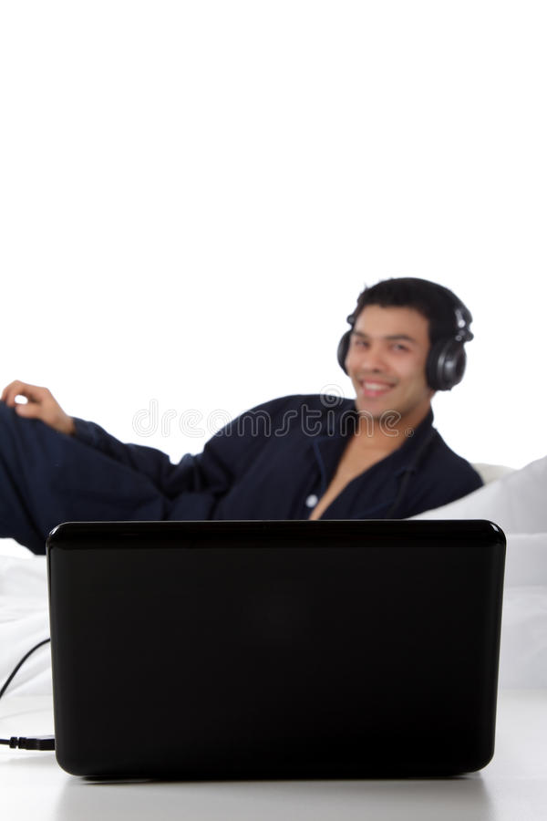 Nepalese man in pajamas, laptop. Handsome young nepalese man in pajamas with headphones and laptop, relaxing in bed and listening music from the internet. Focus stock photo