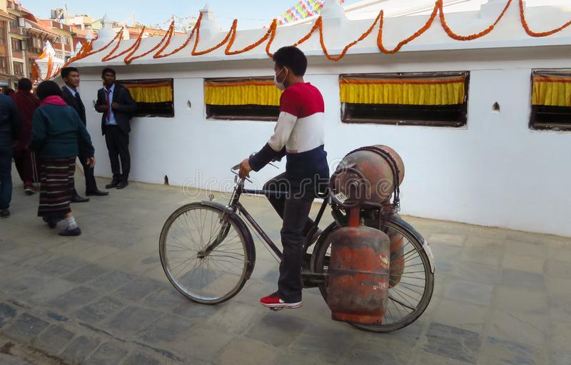 Nepalese man transporting 3 gas cylinders on his bicycle at Bodnath Stupa,. KATHMANDU, NEPAL - 11/14/2017: Nepalese man with protective mask transporting 3 gas royalty free stock photo
