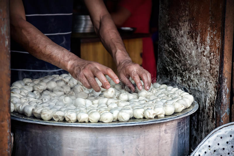 Nepalese momo. BHAKTAPUR, KATHMANDU VALLEY, NEPAL - APRIL 9, 2014: Man cooking steamed traditional Nepalese momos in the street kitchen royalty free stock photos