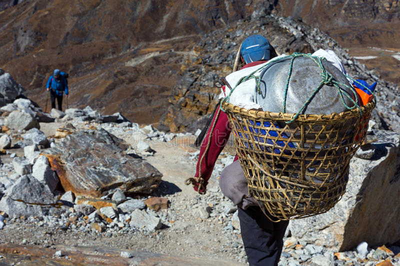 Nepalese Porter carrying Basket with rural household goods. Nepalese Porter carrying traditional handmade Basket with rural household goods using head strap on stock image